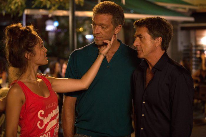 Photo de Lola Le Lann, Vincent Cassel et François Cluzet dans le film Un moment d'égarement de Jean-François Richet. Le Lann touche le visage de Cassel avec un air rieur.