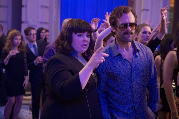 Photo de Melissa McCarthy et Jason Statham dans le film Spy de Paul Feig. Postichés dans une boîte de nuit, les deux espions viennent de repérer leur cible.