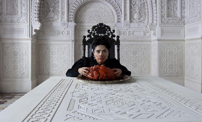 Photo de Salma Hayek dans le film Tale of Tales. La comédienne est assise dans la salle d'un palais blanc et dévore le coeur d'un monstre.