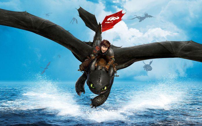 Photo du film Dragons 2. Harold dirige Krokmou au dessus de la mer. D'autres dragons volent derrière eux.
