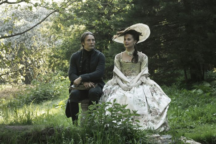 Photo du film Royal Affair. Mads Mikkelsen et Alicia Vikander sont assis côte à côte dans un bois et discutent.