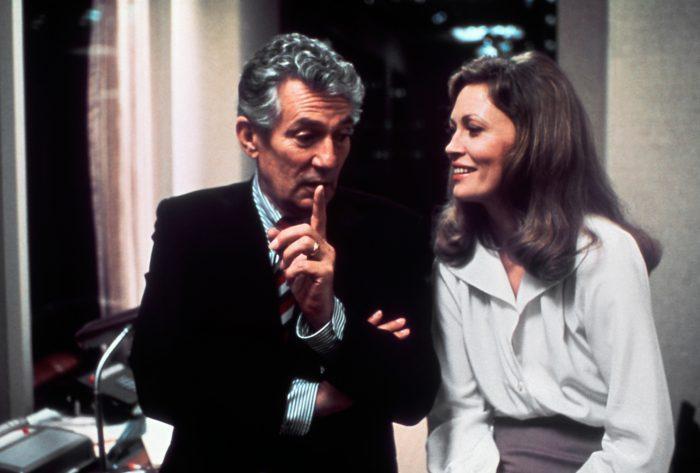 Photo de Peter Finch et Faye Dunaway dans le film Network de Sidney Lumet. Ils discutent et rient côte à côte dans l'un des bureaux de la rédaction de la chaîne de télévision.