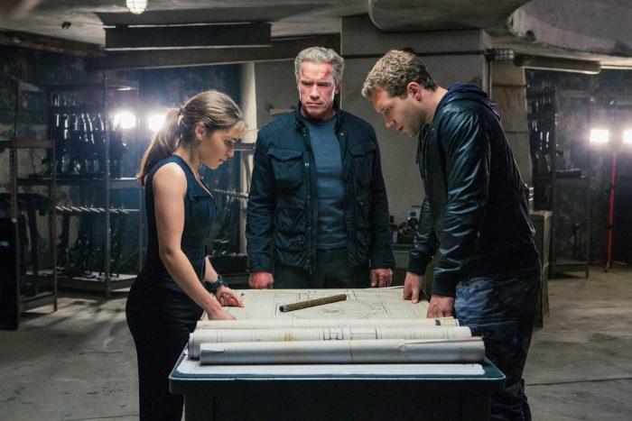 Photo d'Emilia Clarke, Arnold Schwarzenegger et Jai Courtney dans le film Terminator : Genisys. Leurs personnages se tiennent debout autour d'une table et étudient un plan.