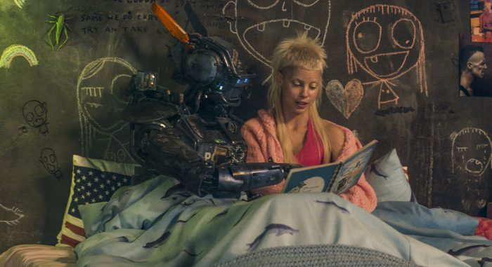 Photo de Sharlto Copley et Yolandi dans le film Chappie de Neil Blomkamp. La chanteuse de Die Antwoord lit une histoire au robot. Ils sont tous deux assis dans un lit et contemplent le livre.