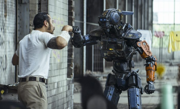 Photo de Jose Pablo Cantillo et Sharlto Copley dans le film Chappie de Neil Blomkamp. Le gangster et le robot sont en train de faire un check amical.