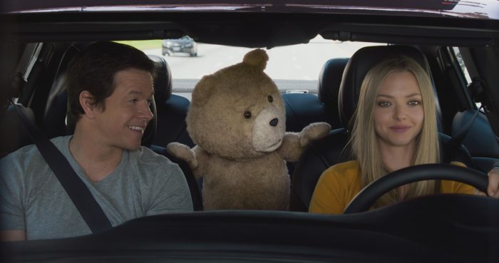 Photo de Mark Wahlberg, Amanda Seyfried et l'ourson Ted dans le film Ted 2 de Seth MacFarlane. Seyfried conduit une voiture en souriant alors que Ted et Wahlberg la regardent et semblent se moquer d'elle.
