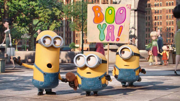 """Photo du film Les Minions. Kevin, Bob et Stuart manifestent avec une pancarte """"Boo Ya !"""" dans les rues de New York."""