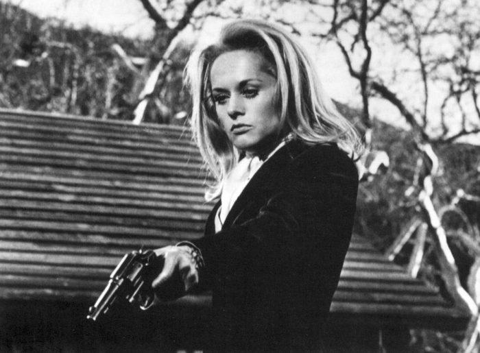 Photo en noir et blanc de Tippi Hedren dans le film Pas de printemps pour Marnie d'Alfred Hitchcock. L'actrice pointe une arme vers le sol avec un regard désespéré.