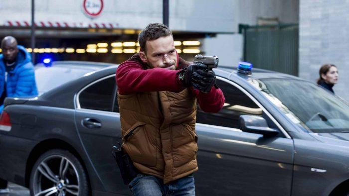 Photo d'Alban Lenoir dans le film Antigang. L'acteur brandit une arme. Deux autres policiers de son équipe se tiennent au second plan, disposés autour de leur voiture.