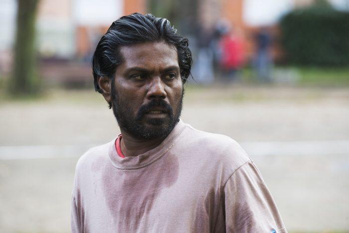 Photo du film Dheepan de Jacques Audiard. Le héros interprété par Antonythasan Jesuthasan se tient debout et en alerte, transpirant.