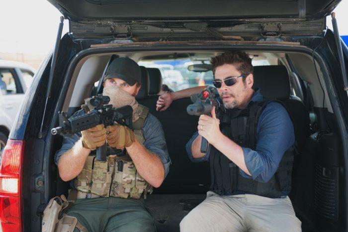 Photo de Benicio Del Toro dans le film Sicario de Denis Villeneuve. L'acteur se tient à l'arrière d'une voiture, coffre ouvert, et brandit son arme pour protéger un cargo accompagné d'un militaire au visage caché.