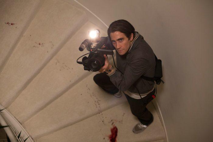 Photo de Jake Gyllenhaal dans le film Nightcall. Le comédien est pris en haut d'un escalier qu'il monte tout en filmant de manière concentrée. Des traces de sang sont visibles sur le sol.
