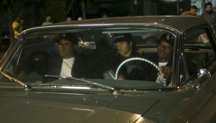 Photo du film Straight Outta Compton. Dr Dre, Ice Cube et Eazy E sont dans une voiture dans une rue qui semble bondée.