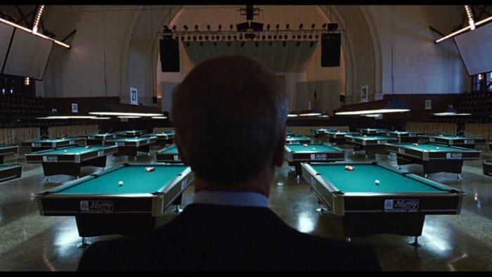 Photo du film La couleur de l'argent de Martin Scorsese. Nous y voyons Paul Newman de dos, en train de contempler une salle de billard vide et éclairée.