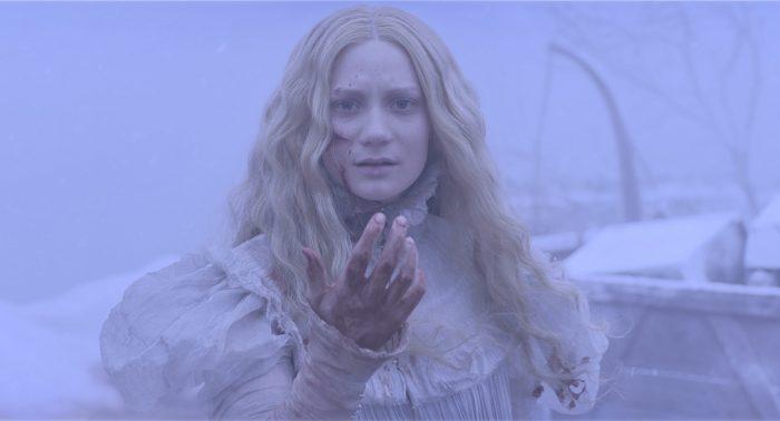 Photo du film Crimson Peak de Guillermo Del Toro. Dans un paysage enneigé et brumeux, l'héroïne incarnée par Mia Wasikowska, vêtue d'une robe blanche tachée de sang, tend sa main vers l'objectif.