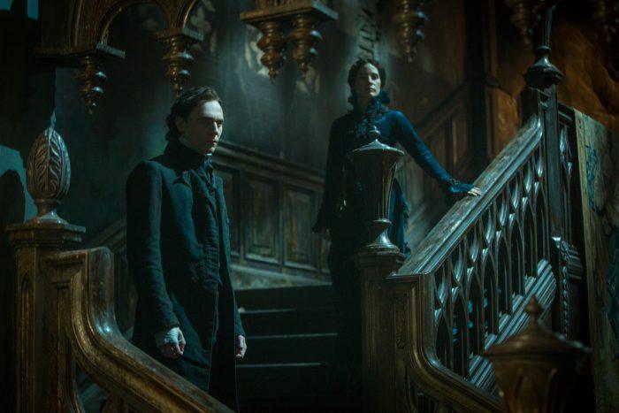 Photo du film Crimson Peak de Guillermo Del Toro. Les personnages incarnés par Tom Hiddleston et Jessica Chastain se tiennent dans l'escalier d'une grande et sombre demeure.