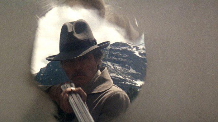 Photo du film La porte du paradis de Michael Cimino. Un drap troué laisse entrevoir le personnage de Christopher Walken qui brandit un fusil avec lequel il vient de tirer.