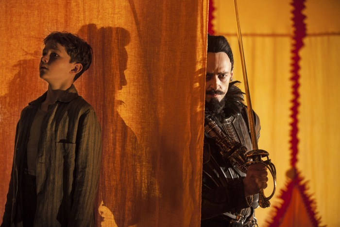 Photographie de Levi Miller et Hugh Jackman dans le film Pan de Joe Wright. Peter Pan se cache tandis que Barbe Noire se tient derrière lui, caché par un drap. Barbe Noire traque Pan.