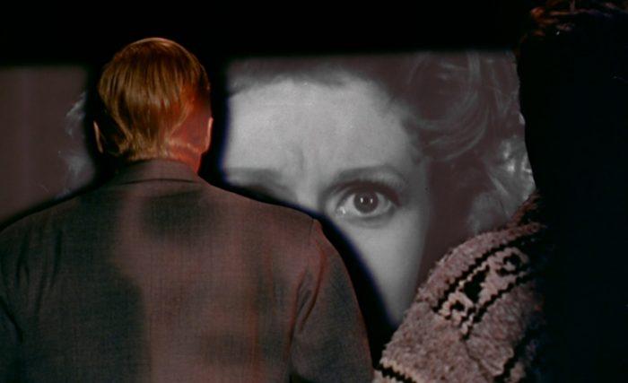 Photo du film Le Voyeur de Michael Powell. Le personnage principal est photographiée de dos, face à un écran de projection duquel il se tient très près.