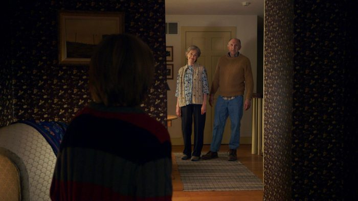 Photo du film The Visit de M. Night Shyamalan. Nous voyons l'un des enfants de dos dans une chambre sombre au premier plan, et ses grands parents au second plan qui semblent le regarder avec tendresse.
