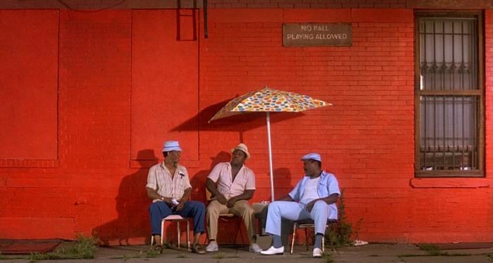 Photographie du film Do The Right Thing de Spike Lee. Devant un mur de brique rouge, trois hommes assez âgés discutent et se protègent de la chaleur.