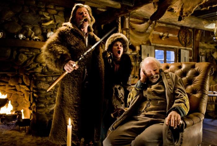 Photographie des Huit Salopards de Quentin Tarantino. Les personnages de Kurt Russell et Jennifer Jason Leigh hurlent, alors que Bruce Dern est assis dans un fauteuil et se couvre une oreille à cause des cris. Russell tient un fusil.