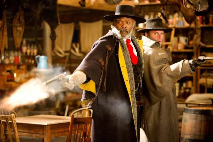 Photographie des Huit Salopards de Quentin Tarantino. Nous y voyons les personnages interprétés par Samuel L. Jackson et Walton Goggins dans le chalet, cadre principal du film. Jackson semble se retourner brusquement et tire un coup de feu vers un personnage que l'on ne voit pas.