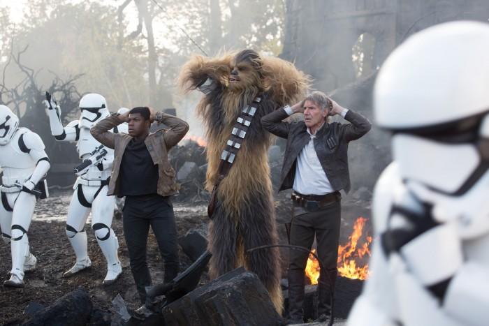Photographie de Finn, Chewbacca et Han Solo dans Star Wars : Le Réveil de la Force. Après une bataille, les trois héros ont les mains derrière la tête et viennent de se faire capturer par des stormtroopers.