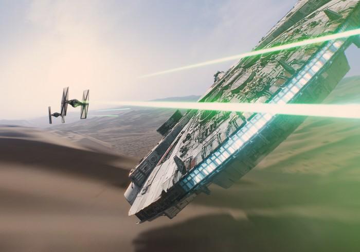 Photo du Falcon Millenium dans Star Wars : Le Réveil de la Force. Le vaisseau évite les lasers des vaisseaux ennemis dans les dunes.