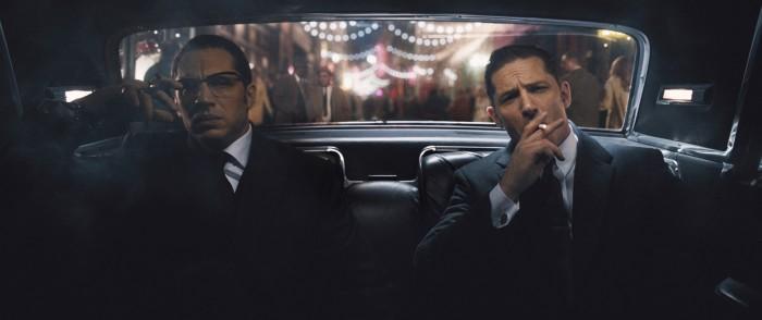 Photographie du film Legend réalisé par Brian Helgeland. Les jumeaux gangsters Kray interprétés par Tom Hardy sont dans une voiture côte à côte. L'un des deux fume une cigarette. Leur voiture roule dans une rue illuminée.