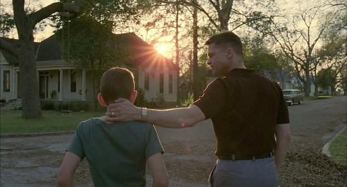Photo de Brad Pitt dans le film The Tree of Life de Terrence Malick. Il pose la main de manière affectueuse sur la nuque de son fils. Ils marchent dans la rue et se dirigent vers leur maison. Le soleil se couche.