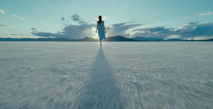 Photographie de Jessica Chastain dans le film The Tree of Life de Terrence Malick. L'actrice est prise de dos, durant un traveling aérien qui s'approche d'elle alors qu'elle marche sur une étendue de sel, face au soleil.