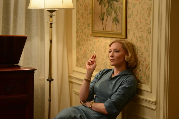 Photographie du film Carol réalisé par Todd Haynes. Nous voyons Cate Blanchett, l'héroïne du film, assise et pensive, en train de fumer une cigarette.