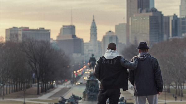 Photo du film Creed, réalisé par Ryan Coogler. Michael B. Jordan et Sylvester sont photographiés de dos en haut du Philadelphia Museum of Art, en train de contempler la ville. Michael B. Jordan a une main posée sur l'épaule de Sylvester Stallone.