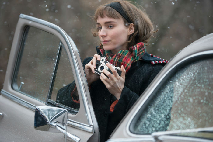 Photogtaphie du film Carol réalisé par Todd Haynes. Nous voyons Rooney Mara, personnage principal du film, en train de prendre une photographie adossée à une voiture.