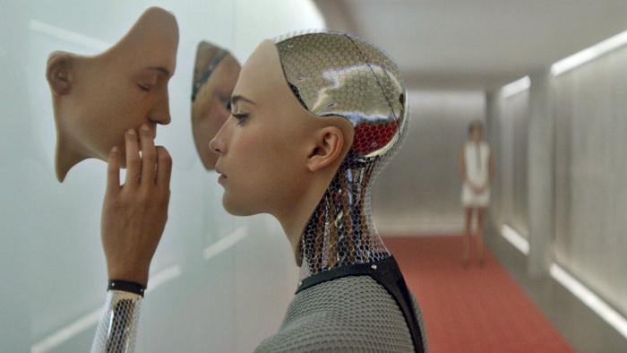 Photo d'Alicia Vikander dans le film Ex Machina d'Alex Garland. Elle y interprète Ava, une intelligence artificielle qui découvre sur la photo un autre prototype de visage robot.