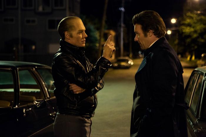 Photographie de Johnny Depp et Joel Edgerton dans Strictly Criminal. Les deux acteurs discutent sur un parking et Depp semble menacer Edgerton en le pointant du doigt.