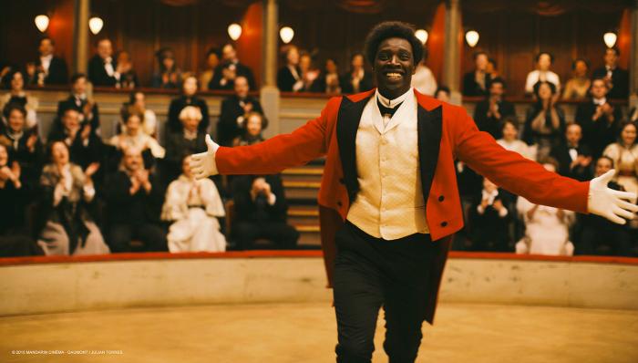 Photographie tirée de Chocolat réalisé par Roschdy Zem. Nous y voyons le clown Chocolat interprété par Omar Sy sur scène, souriant et ouvrant les bras vers le public et l'objectif.