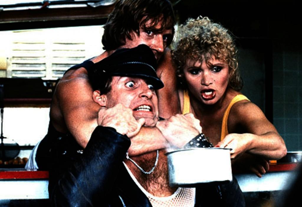 Photographie du film Spetters réalisé par Paul Verhoeven. Nous y voyons deux des personnages principaux retenir un agresseur.