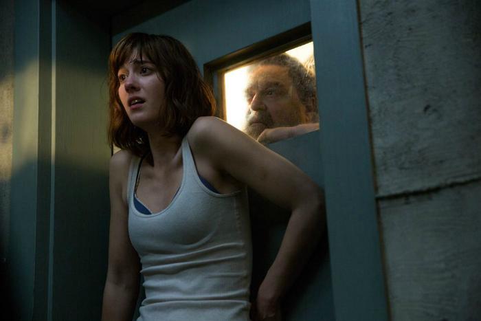 Photo tirée du film 10 Cloverfield Lane réalisé par Dan Trachtenberg. Nous y voyons Mary Elizabeth Winstead enfermée dans un sas, effrayée. Dans une petite vitre derrière, le visage de John Goodman apparaît.