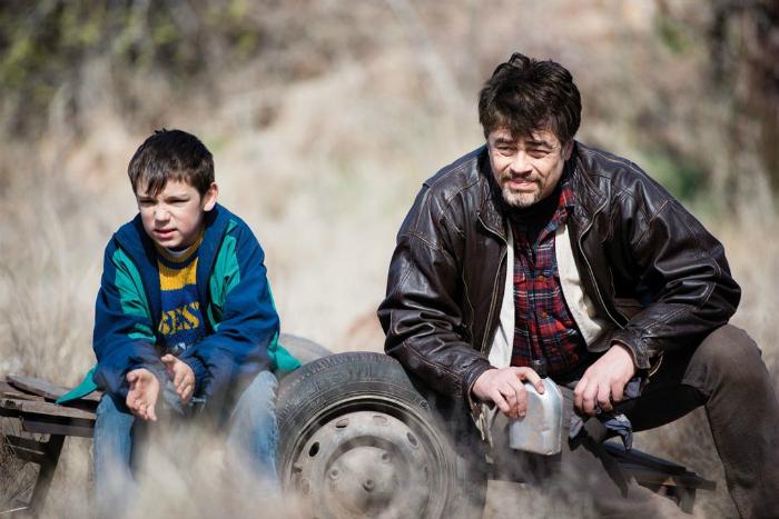 Photographie de Benicio Del Toro dans le film A Perfect Day. Le comédien est assis sur la carcasse d'une voiture retournée avec un enfant. Ils ont l'air complices.