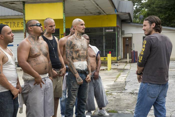 Photo de Casey Affleck dans le film Triple 9 de John Hillcoat. Arme au poing, Affleck porte un tee-shirt de l'unité anti-gang et semble discuter avec les membres d'un gang.