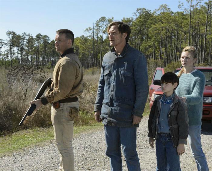 Photo tirée du film Midnight Special. Nous y voyons les personnages interprétés par Joel Edgerton, Michael Shannon, Jaden Lieberher et Kirsten Dunst regarder à l'horizon, sur une route. Leur voiture est derrière eux. Joel Edgerton tient un fusil à pompe.