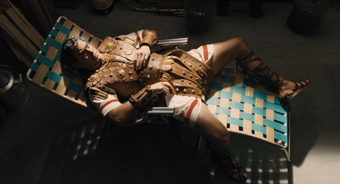 Photo de George Clooney dans le film Avé, César ! réalisé par les frères Coen. Nous voyons Clooney en tenue d'époque romaine allongé sur un transat.