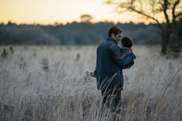 Photo de Michael Shannon et Jaden Lieberher tirée du film Midnight Special. Shannon tient l'enfant dans ses bras et marche dans un champs. On aperçoit au loin le lever du soleil.