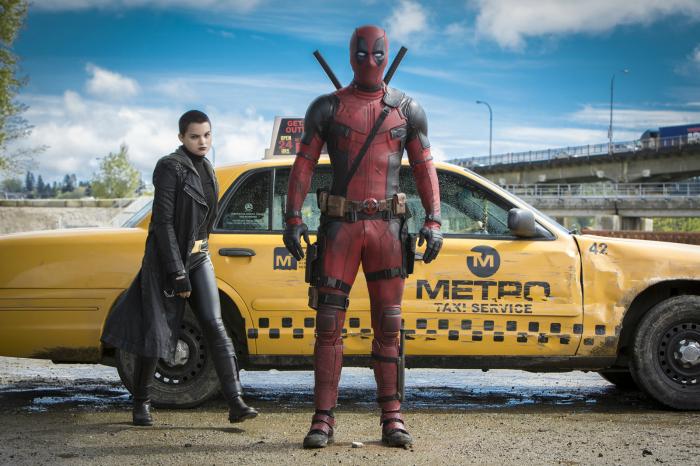 Photogtaphie du film Deadpool de Tim Miller. Nous y voyons le super-héros dans son costume, devant un taxi jaune aux côtés d'une X-Men.
