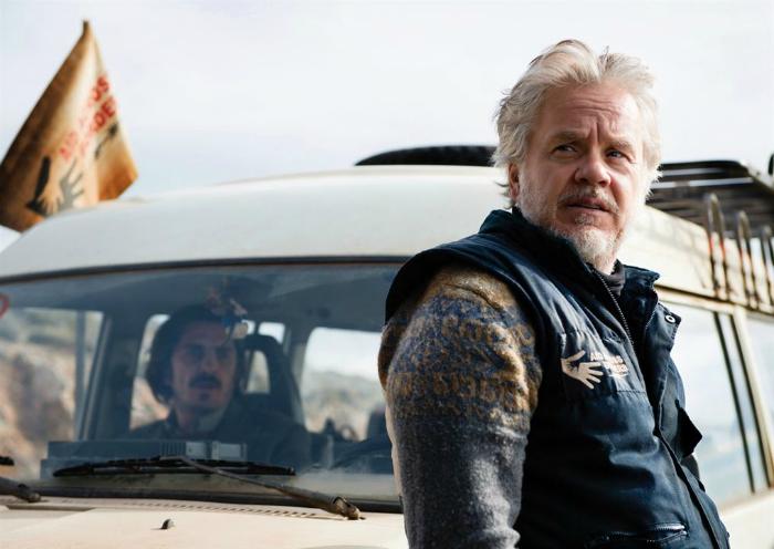Photographie de Tim Robbins dans le film A Perfect Day. L'acteur regarde à l'horizon. Une voiture est derrière lui.