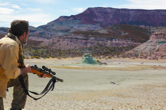 Photo de Jeffrey Dean Morgan dans le film Desierto de Jonas Cuarón. Le comédien est pris de dos, armé d'un fusil et l'on voit au loin les corps des clandestins mexicains qu'il vient d'abattre froidement.