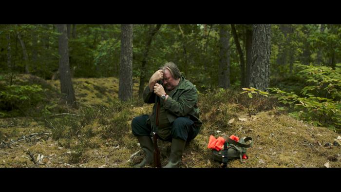 Photographie de Gérard Depardieu dans le film The End de Guillaume Nicloux. Depardieu est assis sur un rocher, la tête penchée sur sa main et son fusil. Il semble dépité.