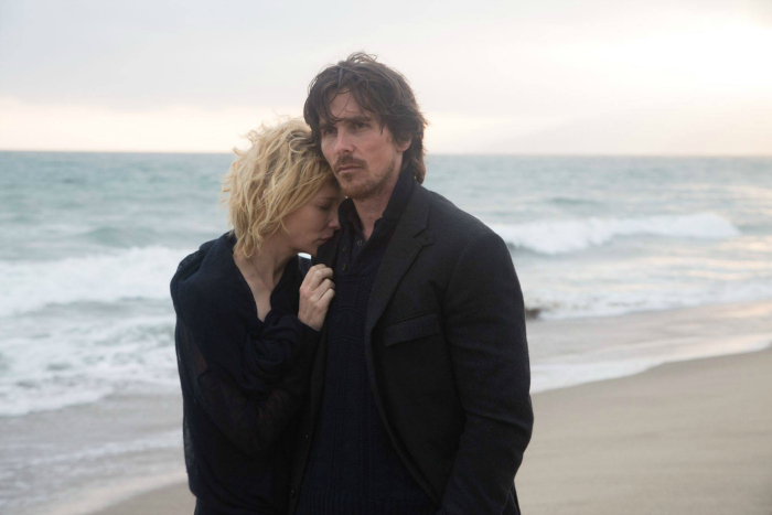 Photographie du film Knight of Cups réalisé par Terrence Malick. Christian Bale et Cate Blanchett marchent sur une plage l'un contre l'autre, vêtus de noir.